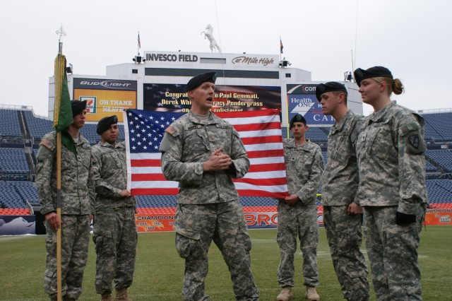 DENVER -- 2nd Lt. Kyle Murphy says a few words before swearing in Spcs. Nicholas Yandell, left, and Tracy Pendergrass during their reenlistment ceremony at INVESCO Field at Mile High Stadium on 28 Jan.