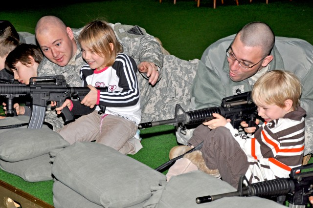 Sgt. Matthew Vanderbeogh (left) of 1st Armored Division gives second-grader Aurora Johnson some pointers while her father, Staff Sgt. Grant Johnson, also of 1st AD, helps his son kindergartner Pierce Johnson take aim in the Wiesbaden Army Airfied Engagement Skills Trainer during Groundhog Job Shadow Day.