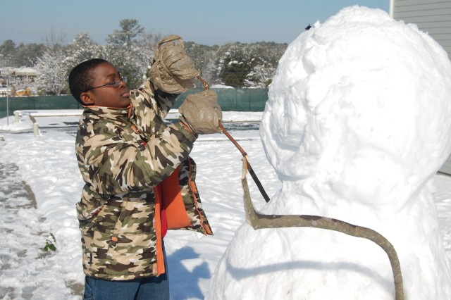 Montrel Jones, 12, adds arms to the snowman he built across the street from his home. Montrel used plastic bags to waterproof his gloves.