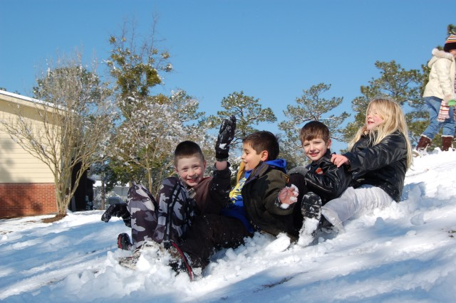 From left to right: Austin Derbyshire, 9, Tomas Oleson, 6, Jacob Calman, 6, and Kacie Rhoados, 8, slide down a snowy hill in the family housing area. (Photo submitted by Fort Jackson resident and spouse MARCELA OLESON.)
