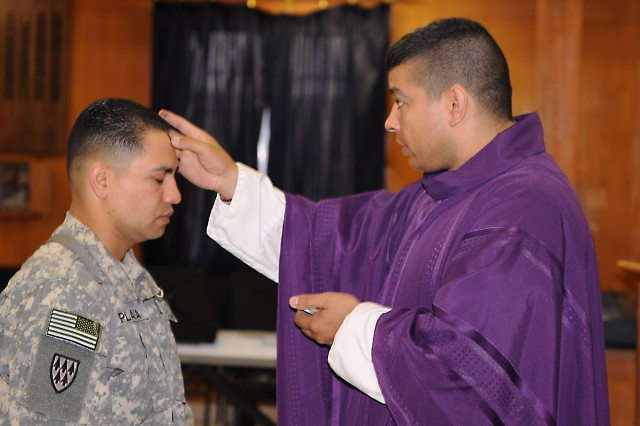 Chief Warrant Officer 2 Louis Plaza, a command and control computer, communications and intelligence system integrator, assigned to Company A, Division Special Troops Battalion, 1st Armored Division, United States Division - Center, receives the sign of the cross made by ash from Capt. Anselmo Hernandez, a Catholic chaplain, at the Division Chapel Feb. 17 during Catholic Mass on Ash Wednesday. Ash Wednesday is the first day of Lent that occurs a total of 46 days before Easter.