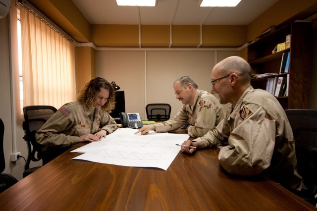 Engineers Christa Besing, left, Mark Hoague, center, and Peter Schei in Kabul review plans for the weld-free water towers.