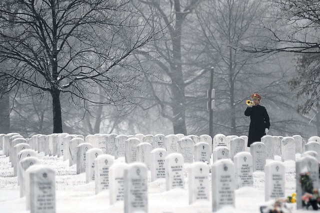 "A bugler from the U.S. Army Band ""Pershing's Own"" plays Taps at a burial service in Arlington National Cemetery."