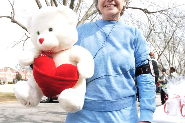 Chiqui O'Leary, a retired Delta Airlines employee, holds a teddy bear she won for getting one of the two specially marked candy mugs. All participants who finished received mugs (below) after the race. The prizes were provided by DFMWR.