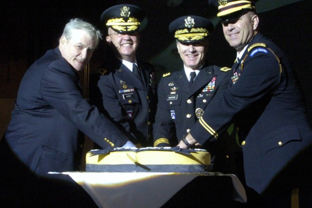 Retired Chief Warrant Officer Pete McDermott (left), an original Fife and Drum Corps member, joins Maj. Gen. Karl R. Horst, MDW/JFHQ-NCR commander; Lt. Gen. David Huntoon Jr., director of the Army Staff; and Chief Warrant Officer Gregory S. Balvanz, Fife and Drum Corps commander, to cut the cake with a sabre in a kick-off ceremony celebrating the Fife and Drum Corps' 50th anniversary.
