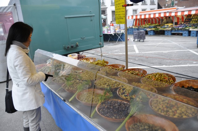 The ChiAfA..vres Garrison Ambassador Program introduces volunteers like Yumi Takushi to the culture and cuisine of Belgium. At the town market in Soignies, Takushi shops for olives. She was the first to formally volunteer for the outreach program.
