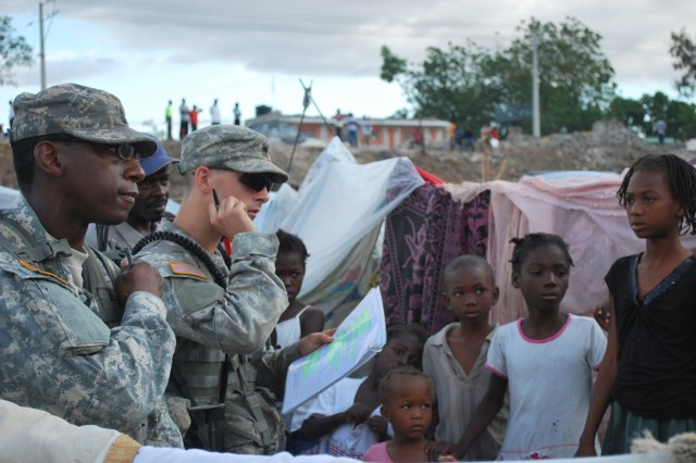 """100218-F-4646B-004 PORT-AU-PRINCE, Haiti (Feb. 18, 2010) Civil affairs soldiers from U.S. Army Special Operations Command speak with children living in a tent city in Port-au-Prince, Feb. 18. The civil affairs team assesses medical, shelter, food and water needs to facilitate humanitarian assistance in the area. (U.S. Air Force photo by 2nd Lt. Victoria Brayton/Released)"""""""