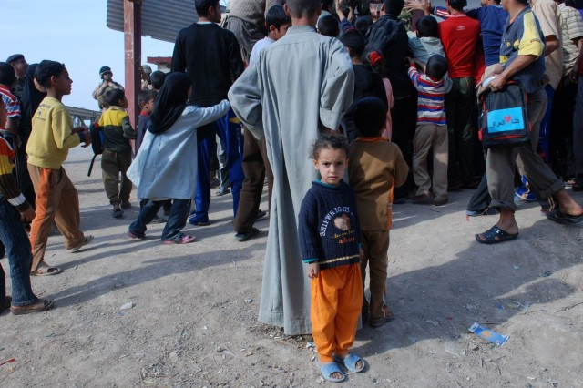 Standing in the security provided by closeness to a familiar adult, a young Iraqi child in the village of Sa'ad, in Basrah Province, is surrounded by the throng of children and adults lining up to receive gifts and school supplies passed out by the Iraqi Army's 52nd Brigade, 14th Division, Feb. 11, 2010. The 52nd Bde. conducted a joint goodwill patrol with the U.S. Army's 5214 Military Transition Team to foster a closer relationship with the local people.