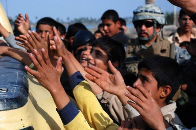 Soldiers from the Iraqi Army's 52nd Brigade, 14th Division, hand out school supplies to children in the village of Sa'ad, in Basrah Province, Iraq, Feb. 11, 2010.  The 52nd Bde., accompanied by the U.S. Army's 5214 Military Transition Team, handed out the supplies and other gifts as part of efforts to create a closer relationship with the local people.
