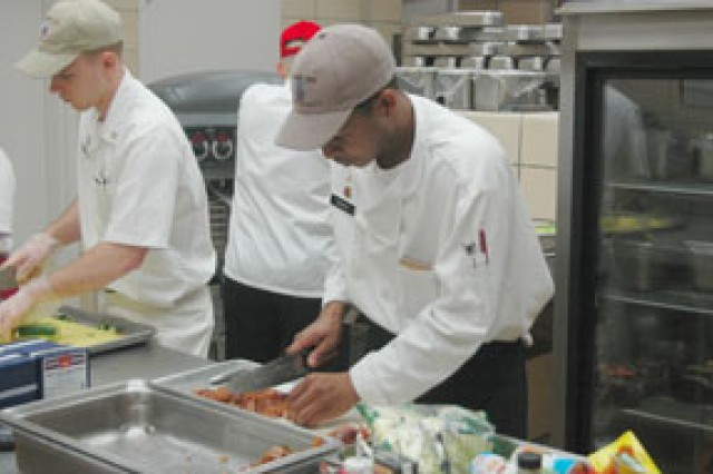 "Pvt. Marcus Barnes, food service specialist, Headquarters and Headquarters Company, 4th Brigade Special Troops Battalion, 4th Brigade Combat Team, 10th Mountain Division, dices bacon during an ""Iron Chef"" competition at Patriot Inn dining facility, Jan. 29."