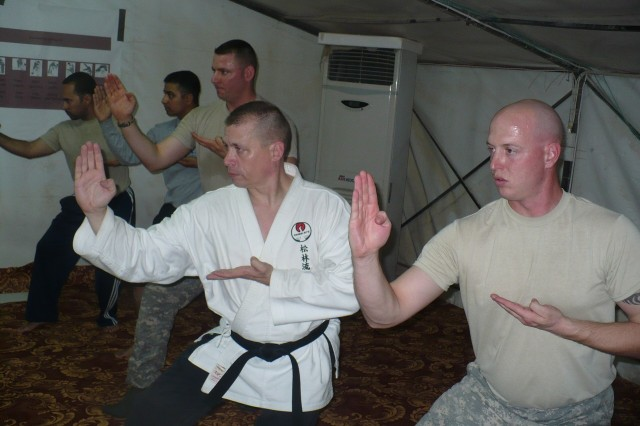 Maj. Rob Boone, a third-degree black belt in Matasubuyashi Shurin-Ryu karate (middle), leads his students through a new series of moves during his class at Contingency Operating Station Shocker, Iraq, Feb. 12, 2010. Boone, who has 12 years of martial arts experience, teaches a nightly class for U.S. Soldiers assigned to 3rd Squadron, 1st Cavalry Regiment, 3rd Heavy Brigade Combat Team, 3rd Infantry Division, and the Ugandan security force members from Saber International who guard COS Shocker.