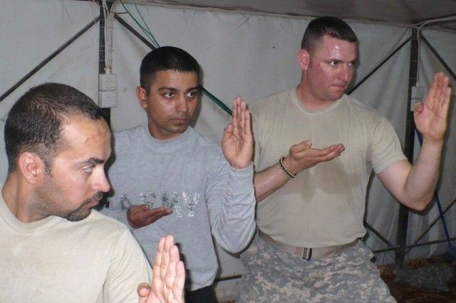Pfc. Falak Mir Shafi (left) and Staff Sgt. Bill Morris, scouts assigned to B Troop, 3rd Squadron, 1st Cavalry Regiment, 3rd Heavy Brigade Combat Team, 3rd Infantry Division, demonstrate martial arts forms during their class at Contingency Operating Station Shocker, Iraq, Feb. 12, 2010. The class, taught by Maj. Rob Boone and his assistant Maj. Charles Krieger, is open to everyone assigned to the small outpost.