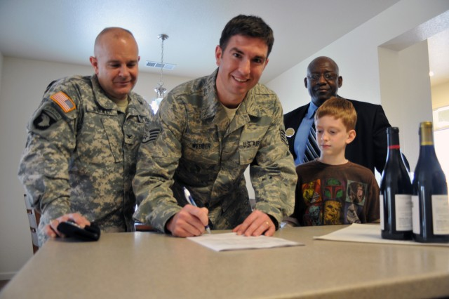 Presidio of Monterey Garrison Commander Darcy A. Brewer watches as Staff Sgt. Gerard Webber signs the first lease in Doe Park Community with son Andrew and Clark Pinnacle OMC manager Dobbie Gordon looking on.