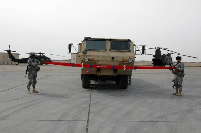 Sgt. Barry Baptiste-Swift (left) and Sgt. Jesus Cuellar, both petroleum supply specialists, Company E, 3-25th General Support Aviation Battalion, Task Force Hammerhead, hold the ends of a ribbon as it is pierced by a M-978 Heavy Expanded Mobility Tactical Truck to celebrate the task force's benchmark accomplishment at Contingency Operating Base Speicher, near Tikrit, Iraq, Feb. 10. TF Hammerhead operates cold fuel operations at COB Speicher and hot fuel Forward Arming and Refueling Point operations at Forward Operating Base Warhorse in Diyala Province. The 1,000,000th gallon of fuel was issued to a CH-47D Chinook helicopter at FOB Warhorse Feb. 9, at approximately 10 p.m.  (U.S. Army photo by Staff Sgt. Mike Alberts, 25th Combat Aviation Brigade Public Affairs)