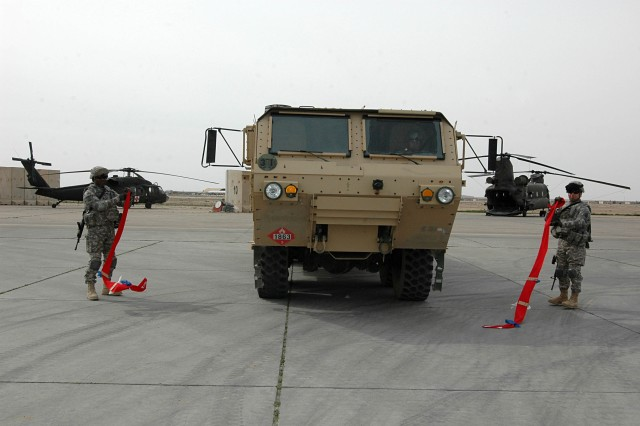 Sgt. Barry Baptiste-Swift (left) and Sgt. Jesus Cuellar, both petroleum supply specialists, Company E, 3-25th General Support Aviation Battalion, Task Force Hammerhead, hold the ends of a ribbon as it is pierced by an M-978 Heavy Expanded Mobility Tactical Truck to celebrate the task force's benchmark accomplishment at Contingency Operating Base Speicher, near Tikrit, Iraq, Feb. 10. TF Hammerhead operates cold fuel operations at COB Speicher and hot fuel Forward Arming and Refueling Point operations at Forward Operating Base Warhorse in Diyala Province. The 1,000,000th gallon of fuel was issued to a CH-47D Chinook helicopter at FOB Warhorse Feb. 9, at approximately 10 p.m. (U.S. Army photo by Staff Sgt. Mike Alberts, 25th Combat Aviation Brigade Public Affairs)