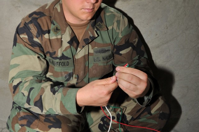 """100217-N-6214F-062 CAP HAITIEN, Haiti (Feb. 17, 2010) Construction Electrician 2nd Class (EXW) Andy Kauffold, of Naval Special Warfare Logistical Support Unit Two, Norfolk, Va., gathers wires that he will use to install an electrical outlet for an improvement project at an orphanage in the city of Cap Haitien. The United States and other international military and civilian aid agencies are conducting humanitarian and disaster relief operations as part of Operation Unified Response in the aftermath of the earthquake. (U.S. Navy photo by Chief Mass Communications Specialist Robert J. Fluegel/Released)"""""""