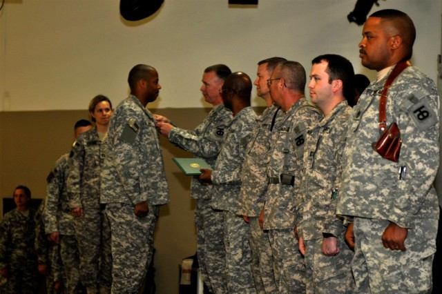 The 90th Sustainment Brigade command staff, out of Little Rock, Ark., 13th Sustainment Command (Expeditionary), pins awards on the brigade's Soldiers at its end-of-tour award ceremony Feb. 15 at Joint Base Balad, Iraq.