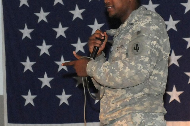 Pfc. Jeremiah G. Taylor, a supply administrator with the 910th Quartermaster Company out of Ardmore, Oklahoma, performs during the Joint Base Balad Poetry Slam at Morale, Welfare and Recreation east Feb. 11 at JBB, Iraq. Taylor, a Memphis, Tenn., native, read poetry to the audience during the event.