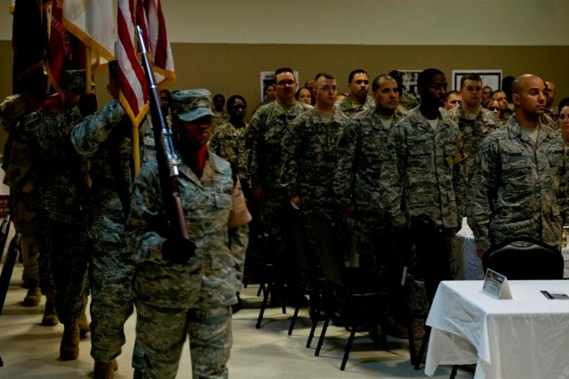 The Joint Base Balad Honor Guard marches and presents the flags in preparation for the singing of the national anthem, during the Black History Month observance luncheon Feb. 19 at Joint Base Balad, Iraq.