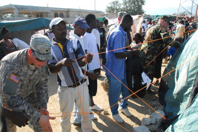 A member of an information support team from U.S. Army Special Operations Command helps several Haitian men set up a new tent at a displacement camp in Port-au-Prince during a humanitarian aid distribution, Feb. 20. The civil affairs team conducted the operation jointly with the 82nd Airborne Division and Shelter Box, a non-governmental organization which provided nearly 100 tents for the camp.