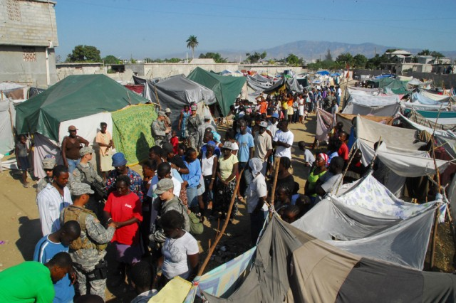 Members of a civil affairs team from U.S. Army Special Operations Command check wristbands of Haitians at a displacement camp in Port-au-Prince, signifying they are to receive a new tent during a humanitarian aid distribution, Feb. 20.