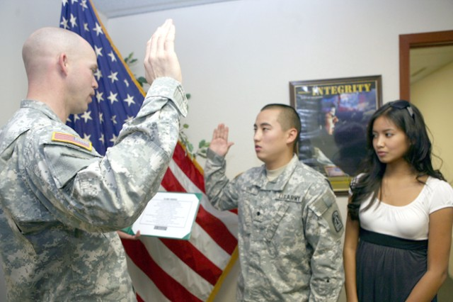 Retention3 - LT. Dan Harris (Left), Charlie Company 86 BSB, reads the oath of reenlistment and swears in SPC Brian Kon, Charlie Company 86 Signal Battalion with his wife Rhra by his side at the Post Retention office bldg, 41414 on post 4 February. Kon plans to reenlist in the Army and move to Long Beach with his wife Rhra were his will be part of the 250 MI Battalion Army Reserve.