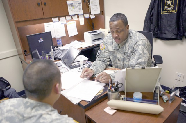 Retention2 - MSG Kenneth Campbell, HHC USAICoE Post Retiontion NCOIC, points to the standard form for reenlistment while SPC Brian Kon, Charlie Company 86 Signal Battalion, awaits to sign his name in the signature block at the Post Retention office bldg, 41414 on post 4 February.  Kon plans to reenlist in the Army and move to Long Beach with his wife Rhra.