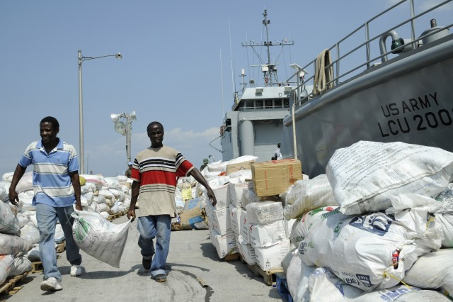 "KILLICK, Haiti - Haitian men carry donated food items down Killick pier to a Colombian Red Cross tent Feb. 16 in Haiti. Army Landing Craft Utility (LCU) 2006 conducted the ""breakbulk"" mission assisting the Colombian Red Cross in getting the loosely packaged donated items off a civilian vessel anchored in Haitian waters and transported them to Killick Pier. (U.S. Army photo by Sgt 1st Class Kelly Jo Bridgwater)"