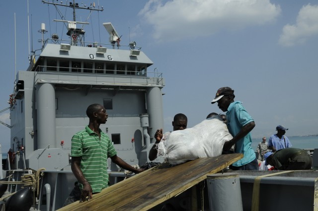 KILLICK, Haiti - Men slide a bag of food down a wooden plank at Killick pier Feb. 16. The food was donated by humanitarian organizations in Colombia to the Haitian people affected by the Jan. 12 earthquake. (U.S. Army photo by Sgt 1st Class Kelly Jo Bridgwater)