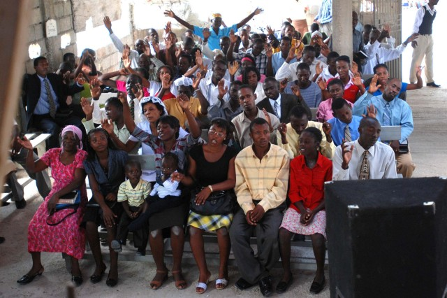 """Locals raise their hands and sing during a church service at the Prophecy Church of God of Caradeux in Port-au-Prince on Feb. 21. Paratroopers with 2nd Brigade Combat Team also attended the service, given by Maj. Brad Baumann, 2BCT chaplain. (U.S. Army photo by Pfc. Kissta M. Feldner, 2BCT, 82nd Abn. Div. PAO)"""""""