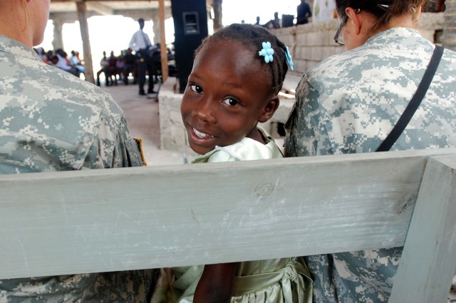 """A local girl sits between two Paratroopers with 2nd Brigade Combat Team, during a church service at Prophecy Church of God of Charadeux, Port-au-Prince on Feb. 21. Maj. Brad Baumann, 2BCT chaplain, conducted the sermon. (U.S. Army photo by Pfc. Kissta M. Feldner, 2BCT, 82nd Abn. Div. PAO)"""""""