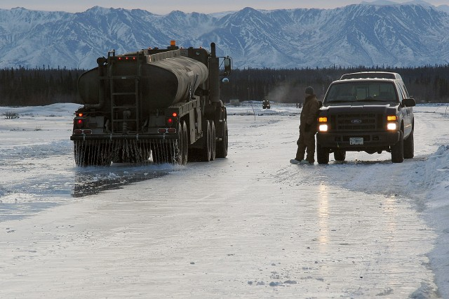 A water truck passes over the ice road spreading a thin layer of water to thicken the ice so it can support heavy equipment transport.