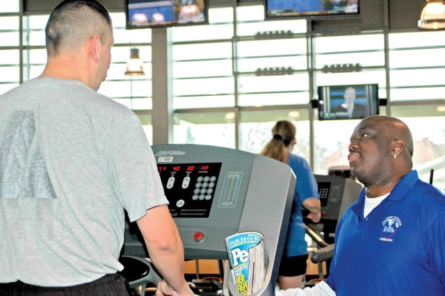 Fitness specialist Leander Townsend talks with Staff Sgt. Calvin Gomez during a Warrior Transition Unit fitness session at the Wiesbaden Fitness Center.
