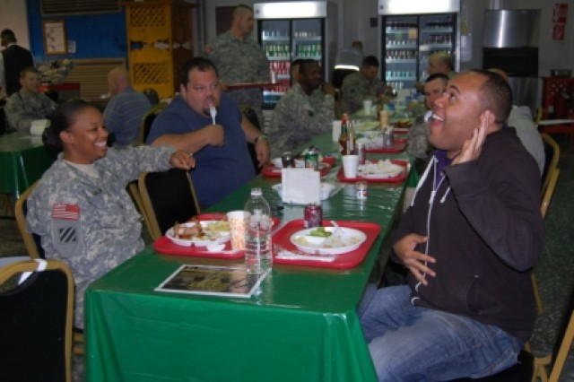 Comedians Chase Durousseau, and Ray Barnett, sit and eat dinner with Sgt. Crystal Thompson, Company F, 1st Battalion, 15th Infantry Regiment, 3rd Heavy Brigade Combat Team, 3rd Infantry Division, before their show Feb. 13, 2010, at Contingency Operating Base Echo, Iraq.