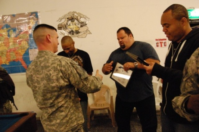 Command Sgt. Maj. Mark Moore, 1st Battalion, 15th Infantry Regiment, 3rd Heavy Brigade Combat Team, 3rd Infantry Division, gives comedians Chase Durousseau, Ray Barnett, and Donnie Johnson certificates of appreciation and battalion coins after their show Feb. 13, 2010, at Contingency Operating Base Echo, Iraq.