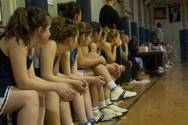 Members of the women's basketball team from Ferizaj/Urosevac, Kosovo, who played on Camp Bondsteel on Feb. 21, watch the action on the court during a game against a group of Camp Bondsteel players.