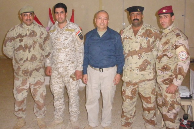 Carlos Legoas, center, stands with four Iraqi noncommissioned officers attending a NCO education brief at the Infantry School in Kirkush, Iraq, Nov. 19, 2009.