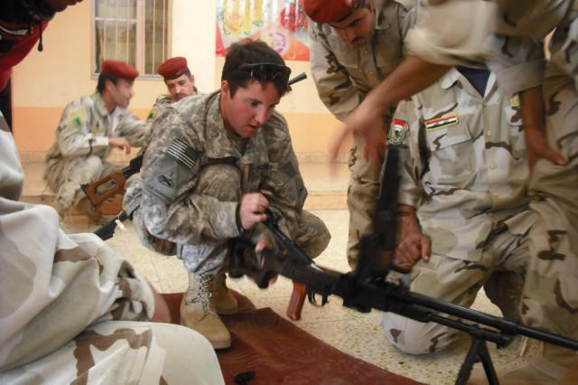 Spc. Daniel Kennedy, from Decatur, Ill., a gunner for C Troop, 2nd Squadron, 13th Cavalry Regiment, works with Department of Border Enforcement guards from the Zaafran Border Fort on assembling one of their crew-served weapons.