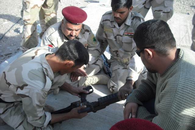 Guards from the Manzaliya Border Fort, 4th Company, 2nd Commando Battalion, 11th Department of Border Enforcement Brigade, work together to reassemble an M-240B machine gun after being taught by more-experienced border guards from Headquarters Company, 2nd Commando Battalion.