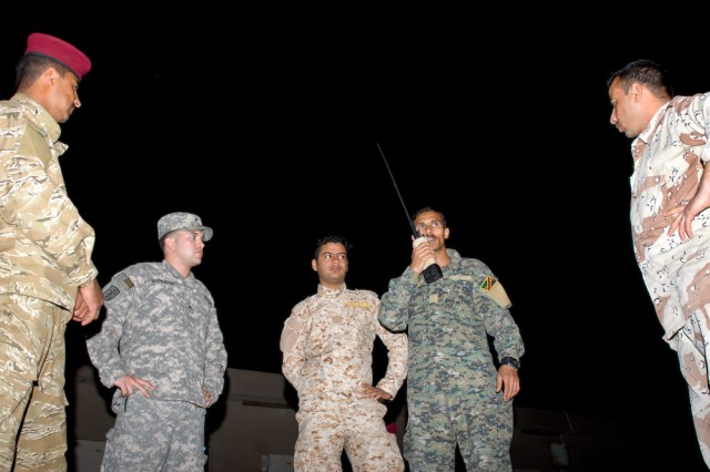 Cpl. Heath N. Kennedy, 256th Signal Company, 17th Fires Brigade, observes and evaluates troops with Signal Company, 14th Iraqi Army Division, Feb. 17, 2010, during a scenario-based night exercise that focused on radioing significant incidents using standard reporting procedures.