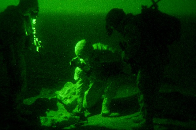 As seen through night-vision optics, Sgt. James Ozsomer, 1st Lt. Pat Barone, and Pfc. John Williams, paratroopers with Company D, 1st Battalion, 504th Parachute Infantry Regiment, 1st Brigade, 82nd Airborne Division (Advise and Assist Brigade), look for evidence of recent smuggling activity while on patrol near the Iraqi-Syrian border Dec. 7, 2009. Barone's platoon was one of many partnering with Iraqi department of border security for training and security operations prior to the 2010 Iraqi national elections.