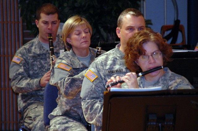 """The woodwind section of """"Pershing's Own"""" rehearses with the rest of the band in Brucker Hall, Fort Myer, Va. Command Sgt. Maj. Debra McGarity (center), adjusts her music during a pause in the performance."""