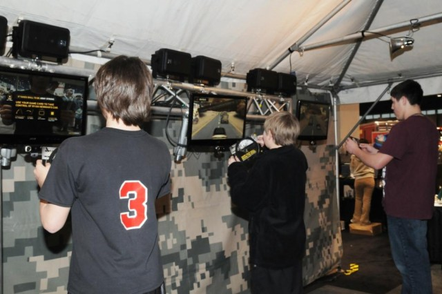 """Eager participants at the Army exhibit for the 2010 Chicago Auto Show, try out the newly unveiled """"Army - Race for Strength,"""" Video Game where they test their skills by navigating through a convoy of Mine Resistant Ambush Protected and Stryker vehicles."""