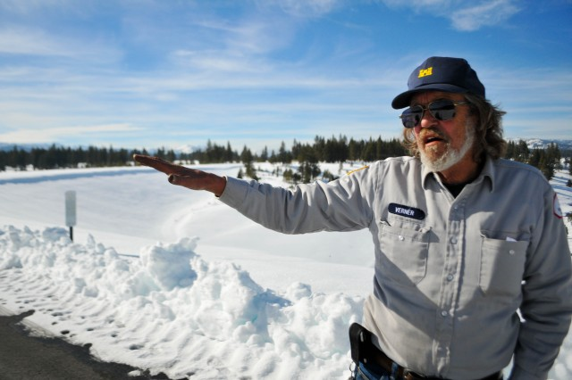 """Dale Verner, dam operator and maintenance worker at Martis Creek Dam in Truckee, Calif., motions toward a frozen Martis Creek Lake while discussing his experience being """"rescued"""" by firefighters during a training exercise."""