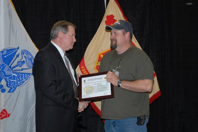 Scott Nahrwold, deputy garrison commander, presents Jeffery Perry, an electronic industrial control mechanic with theDirectorate of Public Works, with a certificate during an Employee of the Month award presentation Tuesday at the Solomon Center. Perry was one of eight garrison employees recognized.