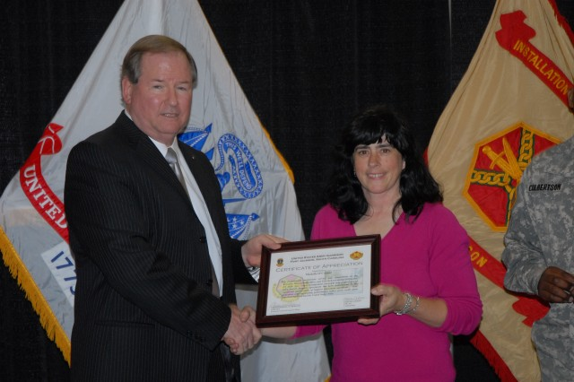 Scott Nahrwold, deputy garrison commander, presents Michelle O'Connor, management analyst with the Directorate of Resource Management, with a certificate during an Employee of the Month award presentation Tuesday at the Solomon Center. O'Connor was one of eight garrison employees recognized.
