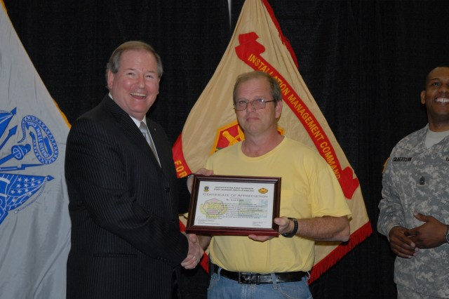 Scott Nahrwold, deputy garrison commander, presents Louis Foster with Directorate of Public Works, with a certificate during an Employee of the Month award presentation Tuesday at the Solomon Center. Foster was one of eight garrison employees recognized.