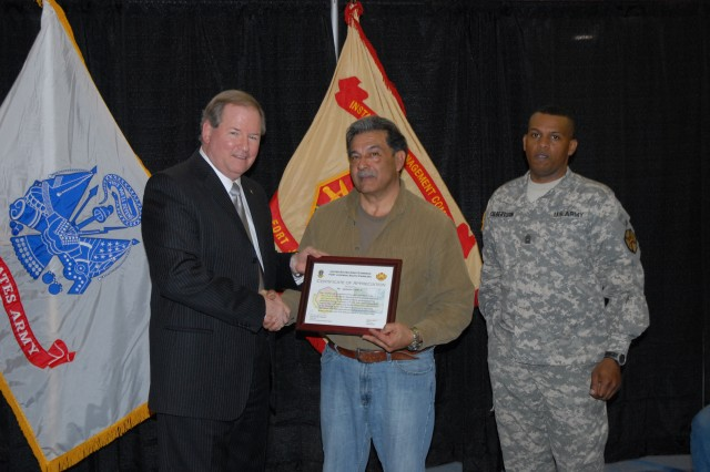 Scott Nahrwold, deputy garrison commander, presents Paul Cantu, a plumber with Directorate of Public Works, with a certificate during an Employee of the Month award presentation Tuesday at the Solomon Center. Cantu was one of eight garrison employees recognized.