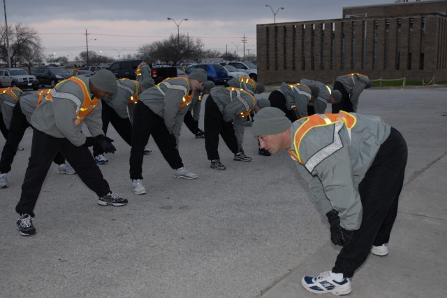 Sgt. 1st Class David Eddington, a human resources non commissioned officer with Headquarters and Headquarters Troop, 3rd Heavy Brigade Combat Team, 1st Cavalry Division who is from Hohenfels, Germany, leads a group of Soldiers in cool-down stretches after his team won the unit's Troop Olympics Feb. 9.