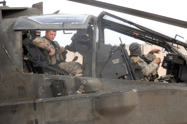 An AH-64D Apache Longbow crew from the 1st Attack Reconnaissance Battalion, 130th Aviation Regiment, prepares for a mission from Contingency Operating Base Delta. The Apache's are now serving as a recon tool for U.S. and Iraqi Forces on the ground as the pilots' mission transitions from close air support to more of a reconnaissance role.